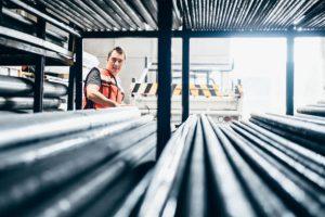 Ouvrier en train de ranger des barres métalliques dans un entrepôt industriel