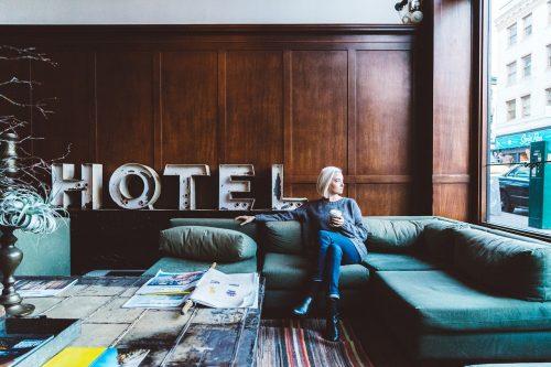 femme assise dans le salon d'un hôtel tenant une tasse à la main